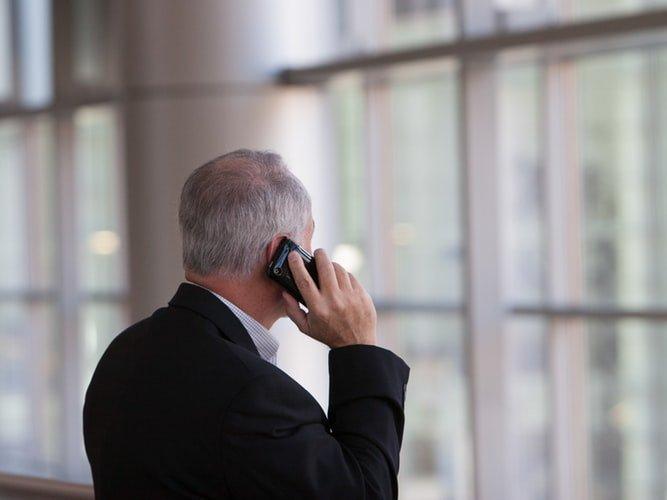 uomo di mezza età parla al telefono